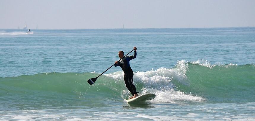 Stand Up Paddling im Meer mit Wellen