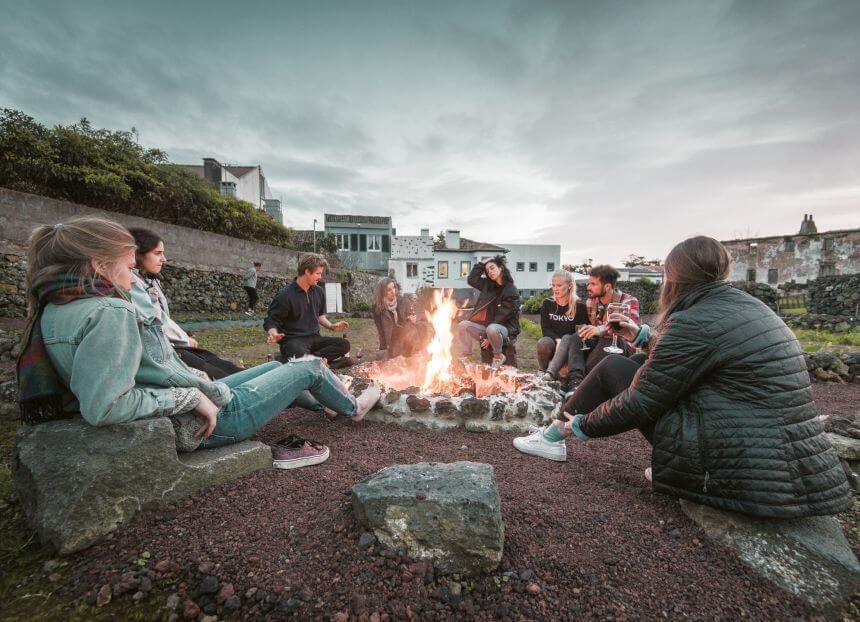 Betreiber Erkik und Joao vom Blacksand Surfcamp Azoren mit den Campgästen beim Lagerfeuer